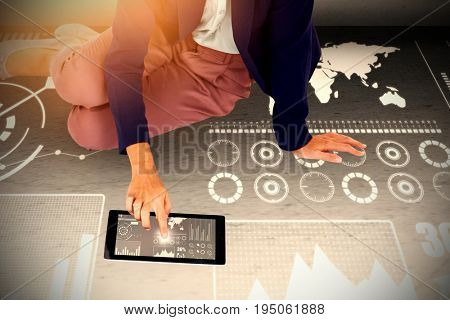 Low section of businesswoman using digital tablet on white background against grey room