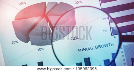 flared figure against high angle view of magnifying glass on graph chart
