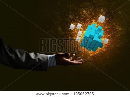 Close of businessman hand holding cube figure as symbol of innovation. 3D rendering