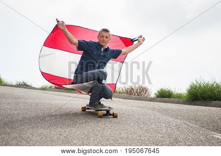 Parachute downhill skateboarder has sail full of wind as he rides in a crouch on his board.