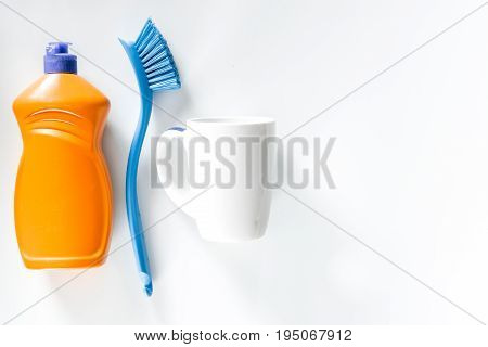 Dishwashing liquid, brushes and tableware on white background top view.
