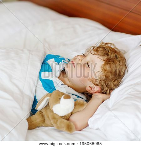 Little blond child sleeping in his bed with toy. Cute kid boy dreaming. Lifestyle, children, home concept.
