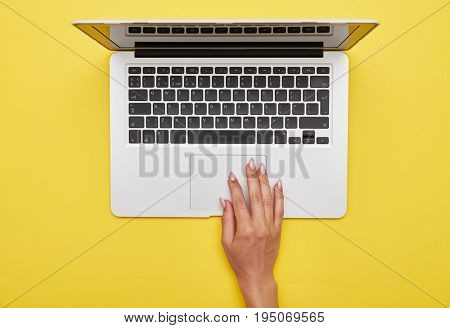 Flat lay of female hand using touchpad of laptop on yellow background