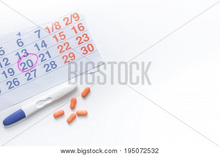 Pregnancy planning. Pregnancy test, calendar and pills on white background top view copyspace.