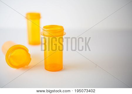 Three Rx vials with copyspace, representing healthcare, science, insurance costs or addiction