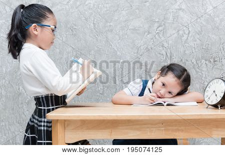 Teacher Writing On Book And Student Bored To Doing Homework