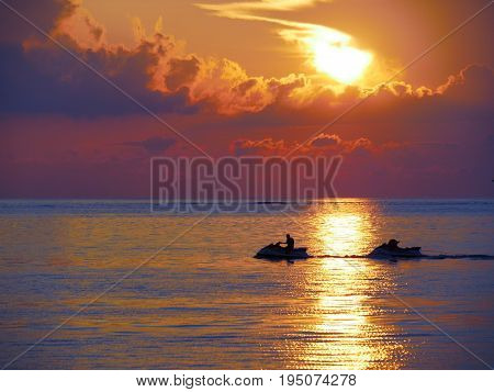 Sunset silhouette of jet ski rider in a tropical island  A jet skier silhouetted against a fiery setting sun reflected in the sea