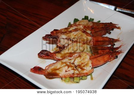 Stuffed grilled prawns Grilled stuffed prawns on a bed of onions topped with sauce and served in a white rectangle plate