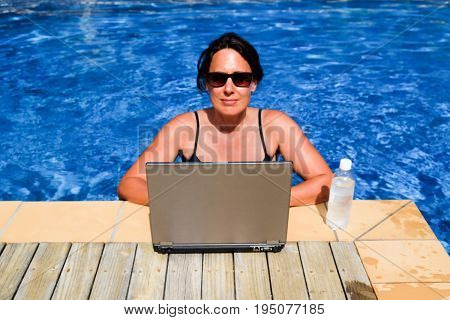 Female executive workaholic working on laptop computer in swimming pool on vacation - work from anywhere concept