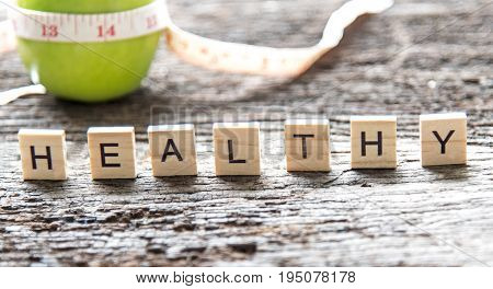 Words of Healthy concepts collected in crossword with wooden cubes. Green apple and measuring tap background. Healthy Concept. select focus