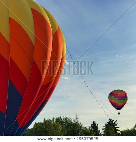 A colorful Hot Air Balloon is ready to ascend while another brightly colored balloon floats by on a sunny Central Oregon morning.