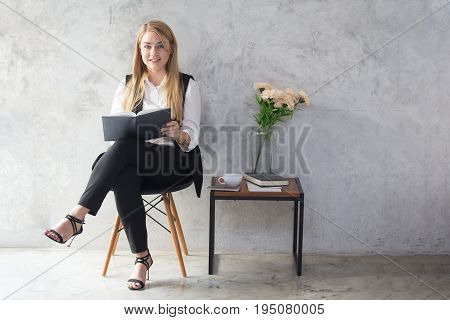 Portrait of a beautiful young woman reading book with attractive smiling 20-30 year old.