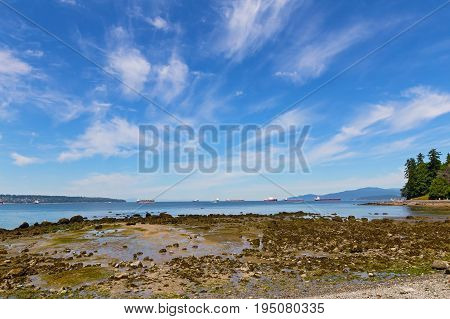 Sea coast during low tide near Stanley Park in Vancouver Canada. Landscape with exposed sea rocks ships and mountains on horizon.