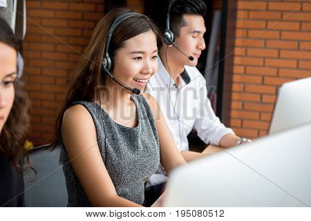 Smiling Asian businesswoman working in call center as an operator or telemarketer