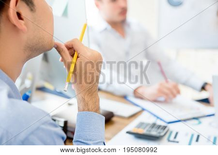 Businessman with hand on chin listening and paying attention to his colleague in the meeting