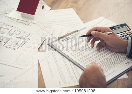 Tenant reviewing rental agreement at the table - real estate and property transaction concept