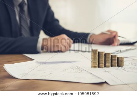 Businessman reviewing document with money and blueprints on the table - real estate and properties investment concepts