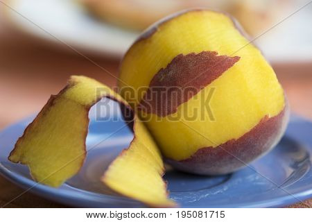 fresh peach peeled on a colored dish