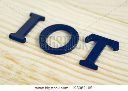 IOT or Internet of Things sign on wood background