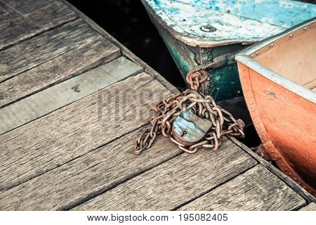 Old iron frayed and shabby boat noses tied to wooden dock close-up