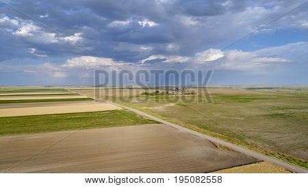 rural Nebraska landscape with prairie, wheat, corn and plowed fields and stormy sky - aerial view