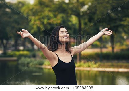 Smiling Vietnamese woman with outstretched arms enjoying sunny day in picturesque park, blurred background