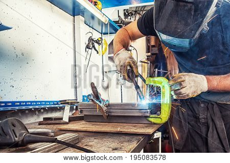 Man Welds A Metal Product