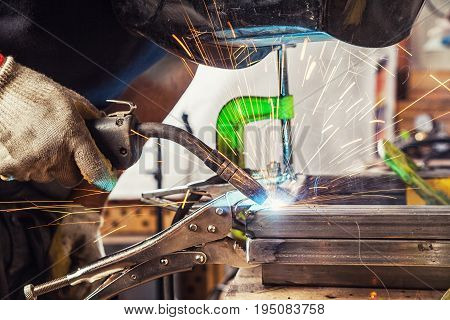 Man Welds A Metal Welding Machine