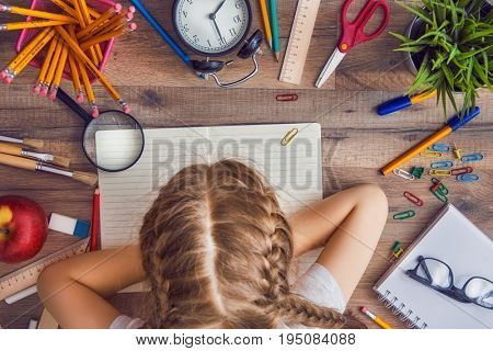 Back to school and happy time! Wooden desk with supplies. A child writes in an empty notebook. Top view.