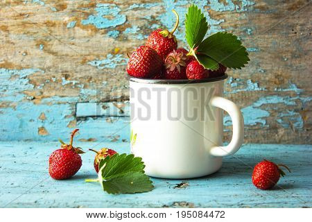 A fresh strawberry berry in an Enameled cup on a blue background