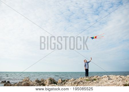 handsome small boy holding a kite flying in the sky standing on the rock on the background of sea