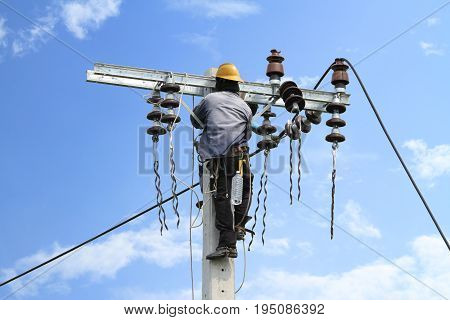 Electrician working on high electric power pole