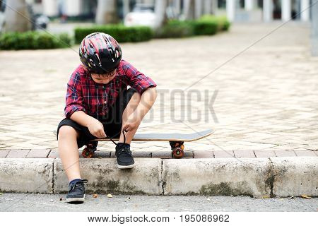 Little skateboarder sitting on pavement and tying shoes before training