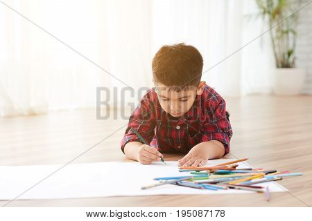 Talented little boy lying on the floor in light room and drawing with pencils