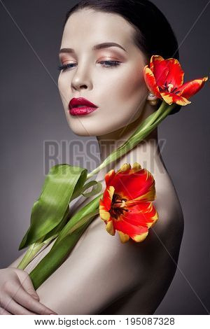 Nude Naked girl with tulips flowers in hand and perfect skin sexy naked brunette woman to gray background. Skin care of face and hands in the summer. Bright natural makeup