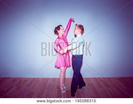 The young boy and girl posing at dance studio on blue in tango posture. The ballroom dancing concept
