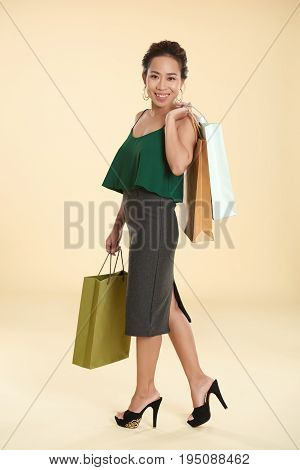 Full-length portrait of Vietnamese female shopaholic with many purchases