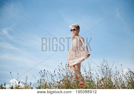 beautiful young caucasian girl wearing short dress and trendy sunglasses among summer field with flowers with blue sky background