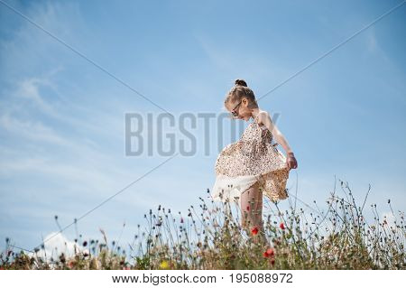 beautiful little girl in sunglasses plays with her dress blown by wind on blue cloudy sky background