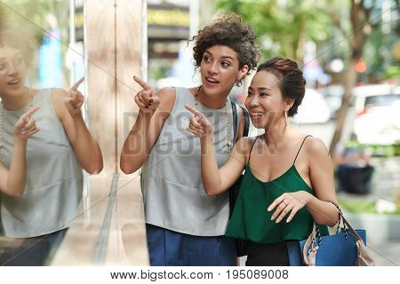Female friends looking at something in showcase