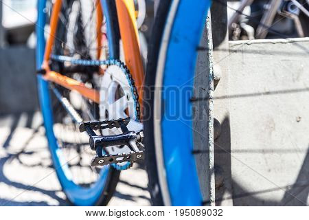 Closeup of blue, orange and white hipster urban bicycle. Focus on chainring.