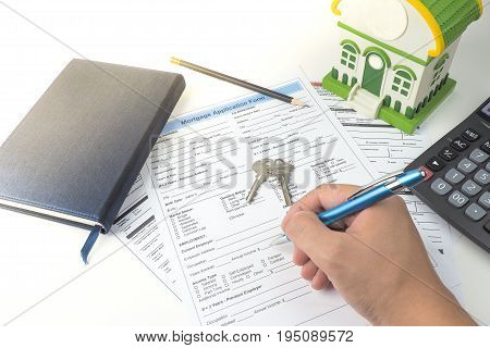 Mortgage application form top view house model notebook calculator pen pencil and key with hand business mortgage concept
