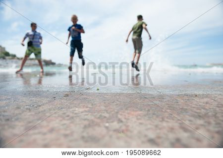 Three young boys run away from surging waves out of focus