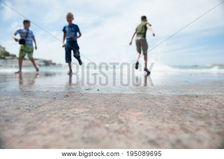 Three little boys run away from surging waves out of focus