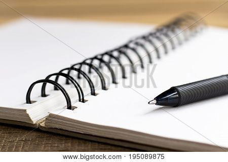 pen and white notebook on wooden table.
