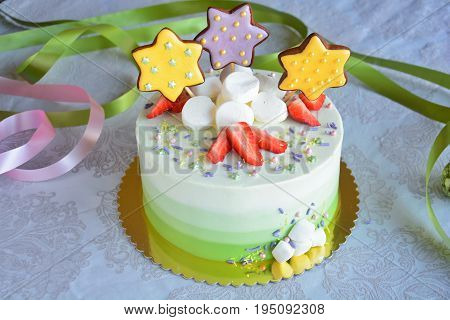 White and green ombre cake with strawberries marshmallows and gingerbread stars on white background