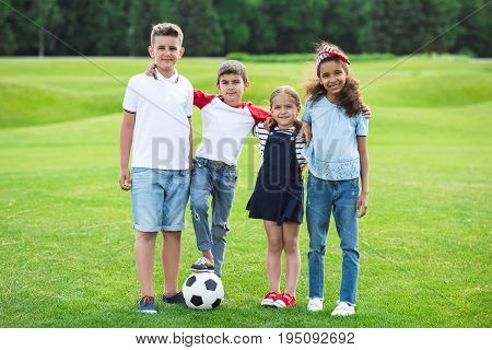 Adorable Multiethnic Kids Standing With Soccer Ball And Smiling At Camera In Park
