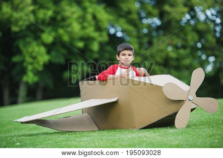Cute Little Boy Sitting In Toy Plane While Playing In Park