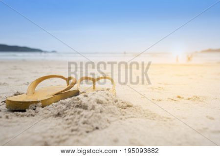 Summer holiday on the beach yellow sandals on the beach have sunset