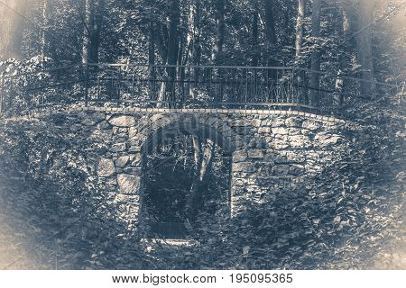 Old vintage photo. Bridge stones sunny day shadow park forest leaves copy space